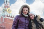 Young man and woman stand near Spasskaya tower on Red Square in Moscow at winter day.