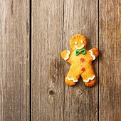 stock photo of ginger man  - Christmas homemade gingerbread man over wooden table - JPG