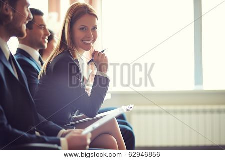 Row of business people sitting at seminar, focus on attentive young female poster