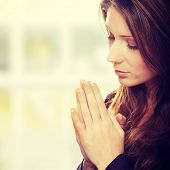 stock photo of sorrow  - Closeup portrait of a young caucasian woman praying - JPG