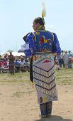 Unidentified female Native American dancer wears traditional Pow Wow dress