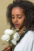 Beautiful Ethiopian young woman in traditional dress holding white roses