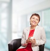 foto of 55-60 years old  - attractive woman 50 years old with cup of coffee - JPG