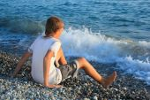 Sitting Teenager Boy On Stone Seacoast, Wets Feet In Water, Sitting By Back