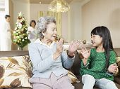 stock photo of grandma  - grandma and granddaughter playing on couch at home - JPG