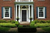 stock photo of front door  - Red brick house with black shutters and green shrubs with front door flanked by pillars and two flower iron urns - JPG