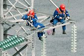 stock photo of lineman  - industrial wiremen on the high voltage mast - JPG