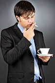 Young Business Man Having A Break Drinking Coffee And Smoking A Cigarette