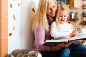 Mother reading tired daughter good night story out of storytelling book
