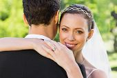 Closeup portrait of beautiful bride embracing groom in garden