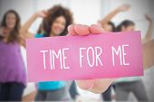 Woman holding pink card saying time for me against class in gym