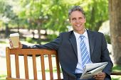 Portrait of smiling businessman with newspaper and coffee cup sitting on park bench