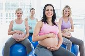 Smiling pregnant women sitting on exercise balls in a fitness studio