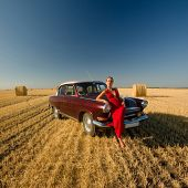 Girl Leaning On Retro Car With Straw Bales Background.