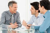 Group Of Happy Businessmen Having Conversation In Meeting
