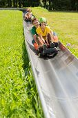 stock photo of luge  - Happy young couples enjoying alpine coaster luge during summer - JPG