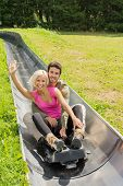 foto of luge  - Portrait of happy young couple enjoying summer sledge ride - JPG