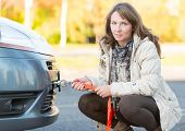 stock photo of towing  - Beautiful woman assembling rope to a towing hook and holding tow rope in the other hand - JPG