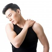 Asian young man having shoulder pain, closeup portrait on white.