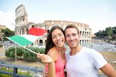 Italy travel couple with Italian flag by Colosseum embracing. Happy tourists lovers on honeymoon sig