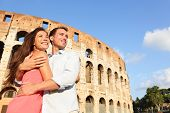 Romantic travel couple in Rome by Coliseum embracing in Italy. Happy lovers on honeymoon sightseeing