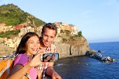 Selfie - couple taking picture in Cinque Terre, Italy with smartphone. Couple taking self portrait p
