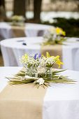 flowers in mason jars on tables for reception