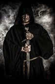 foto of cloak  - Portrait of a courageous warrior wanderer in a black cloak and sword in hand - JPG