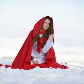 beautiful woman with red cloak sitting on the snow in winter