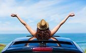 picture of rest-in-peace  - Rear view of relaxed woman on summer travel vacation to the coast leaning out car sunroof towards the sea.