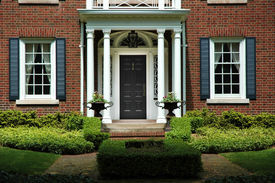 picture of front door  - Red brick house with black shutters and green shrubs with front door flanked by pillars and two flower iron urns - JPG