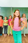 Girl stands with arms on hips near blackboard