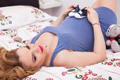 Pregnant Young Woman Laying On The Bed