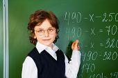 Clever boy holds chalk near blackboard