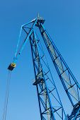 Upper Part Of Big Industrial Port Crane Above Blue Sky