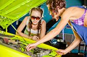 Two Female Auto Mechanic Repairing A Car