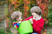 Laughing Boy Playing With His Little Baby Sister In A Laudry Basket In The Garden