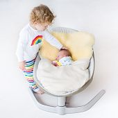Tiny Newborn Baby Sleeping In A Swing On A Sheepskin With His Toddler Sister Next To Him