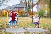 Happy Laughing Boy And His Little Baby Sister Playing Together On A Swing In Autumn