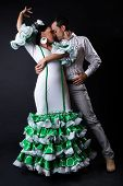 Young Flamenco Dancers In Beautiful Dress On Black Background.