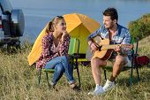 foto of serenade  - Cute man serenading his girlfriend on camping trip on a sunny day - JPG