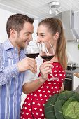 Loving couple drinking red wine in the kitchen