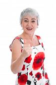 Isolated portrait of successful senior woman in floral dress with thumbs up over white background.
