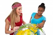 Happy Caucasian and African women posing with globe