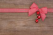 Wooden red christmas background with a white checked ribbon