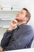 Side view of young businessman thinking in office