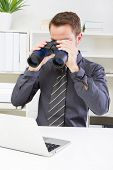 Young businessman looking screen with binoculars