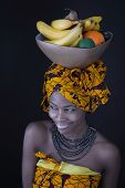 Portrait of a young African woman in traditional dress with a bowl of fruit on her head.