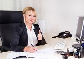 Successful businesswoman sitting in her office with thumbs up.