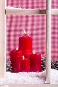 Indoor Christmas window sill decoration: red candles,snow and pine cones on chequered background.